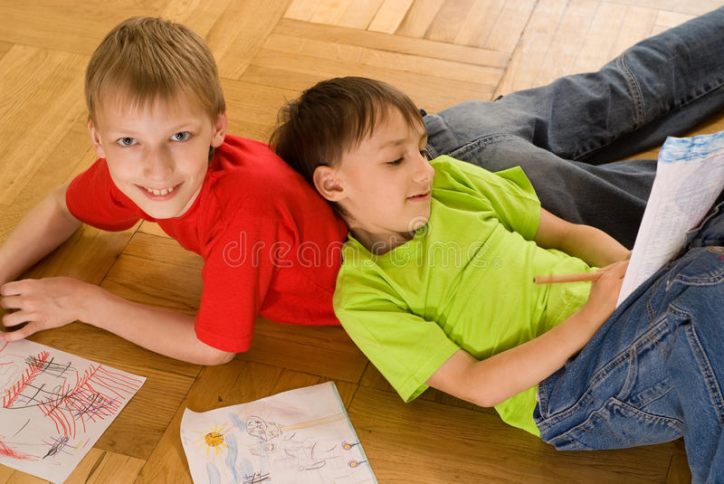 Two brothers draw. Two brothers lying on the floor and draw stock photo