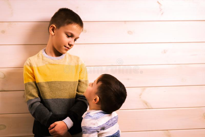 Two brothers - the elder brother and the younger brother, talking in the house against the background of a white wooden wall.  royalty free stock photos