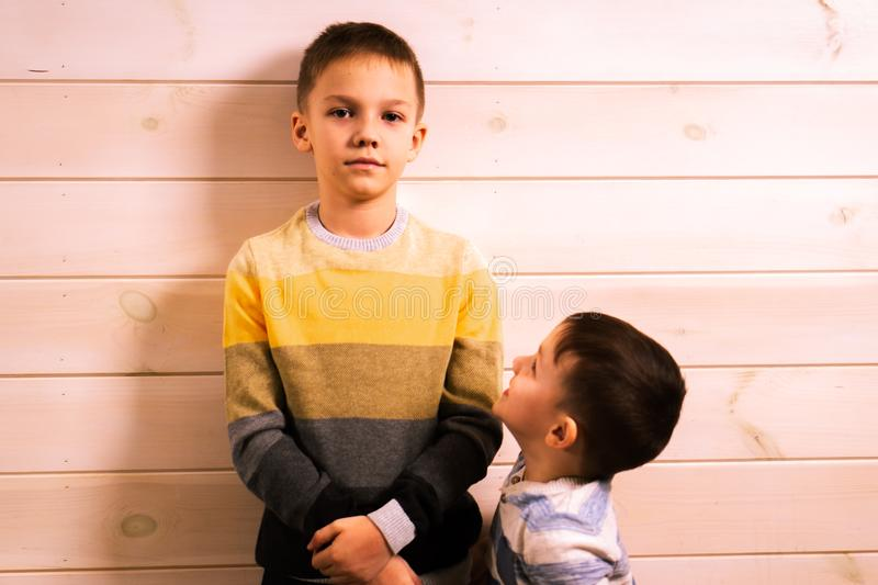 Two brothers - the elder brother and the younger brother, talking in the house against the background of a white wooden wall.  royalty free stock photography