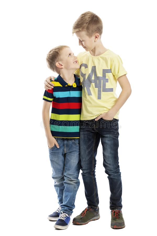 Two brothers embrace and smile, looking at each other. Friendship and love. Isolated on a white background. royalty free stock image