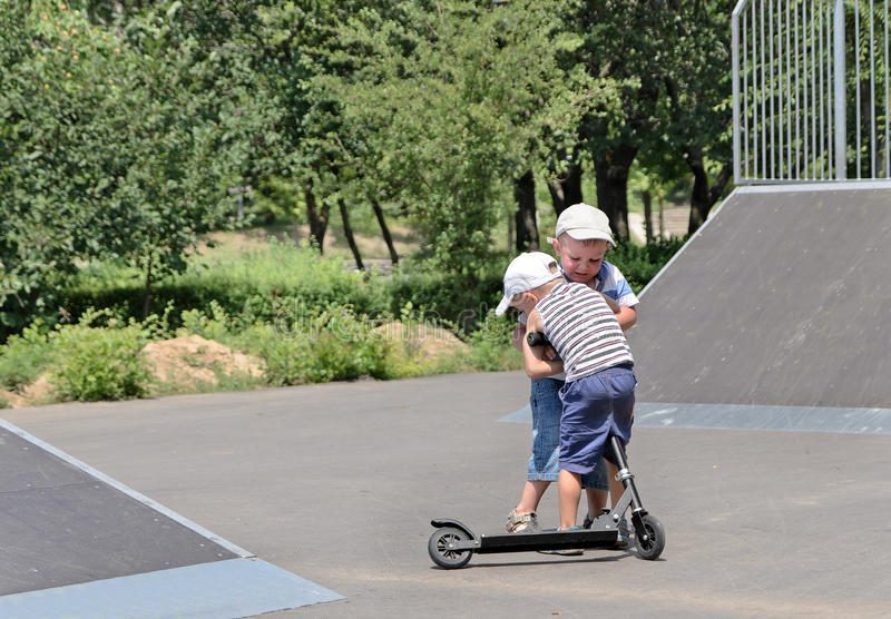Two brothers fighting over a scooter. Two young brothers fighting over a toy scooter in a skate park having a tussle as to who will ride it next royalty free stock photo