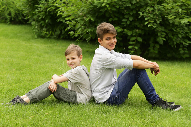 Two brothers have fun in the park - summer time stock photography