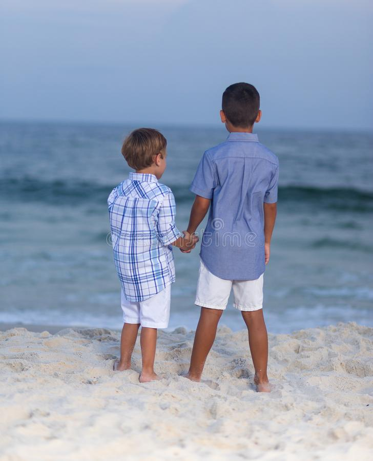 Two brothers holding hands on beach stock photography