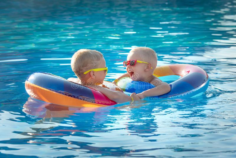 Two brothers in inflatable swimming circles in the pool on hot summer day.Children play in tropical resort. Family beach vacation stock images
