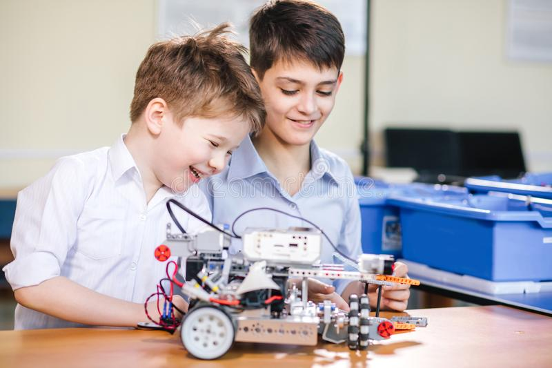 Two brothers kids playing with robot toy at school robotics class, indoor. royalty free stock photography