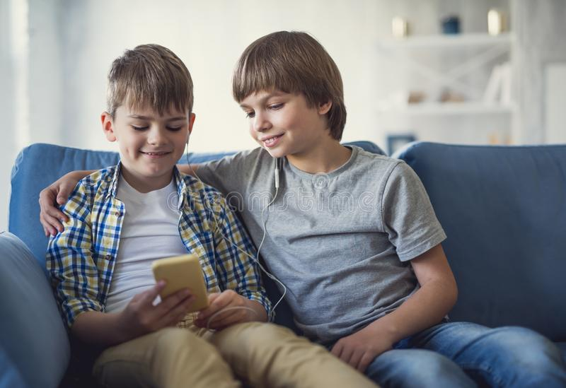 Two brothers listening to music and looking glad stock photo