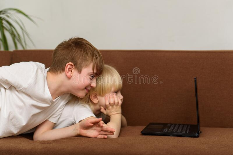 Two brothers lying on couch and stare at laptop monitor. Children watch cartoons.  stock photos
