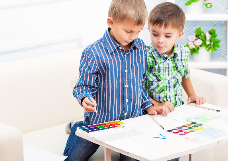 Two brothers are painting something stock photos