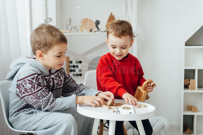 Two brothers play puzzle on the table in the children`s room in the Scandinavian style stock photos