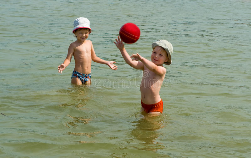 Two brothers playing with ball in the sea stock images