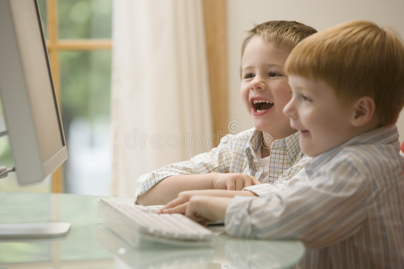 Two brothers playing computer games. Young boys having fun at the computer stock image
