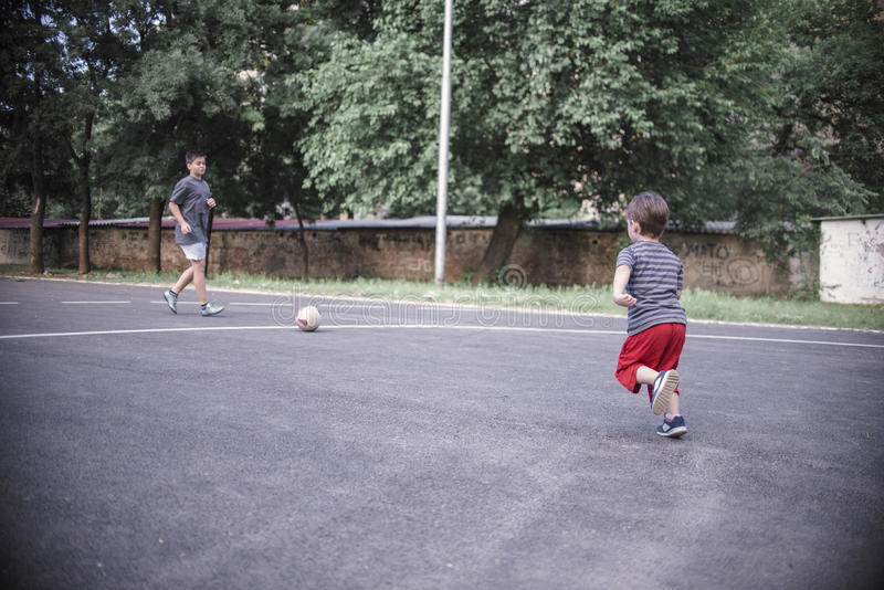 Two brothers playing football royalty free stock image