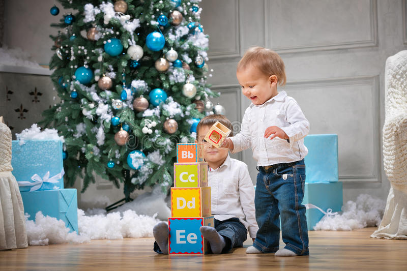 Two brothers playing with wooden alphabet blocks against Christmas tree. At home royalty free stock image