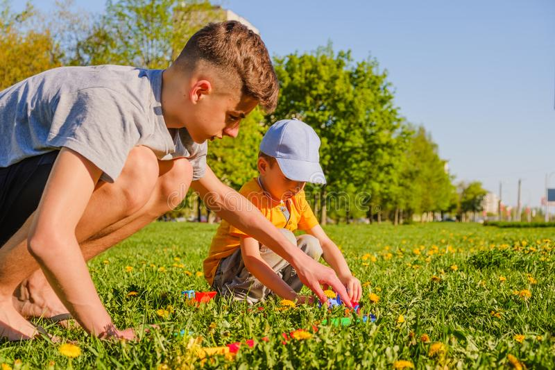 Two brothers plays with a toy car on the green grass lawn royalty free stock photo