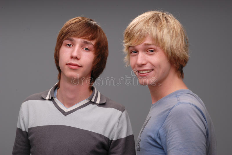 Two brothers, portraits,. Shooting of two brothers in the studio, black hair and blond, two adult young man, and fooling around like kids royalty free stock photo