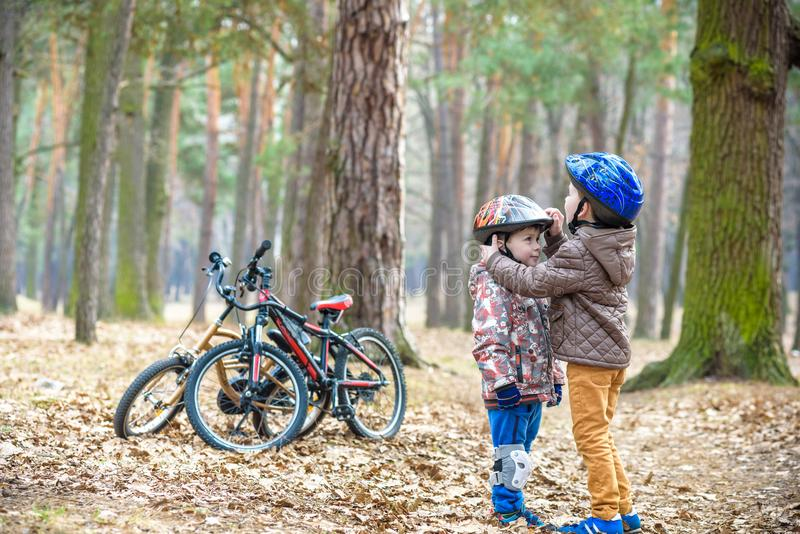Two brothers preparing for bicycle riding in spring or autumn forest park. Older kid helping sibling to wear helmet. Safety and p. Rotection concept. Happy boys royalty free stock photo