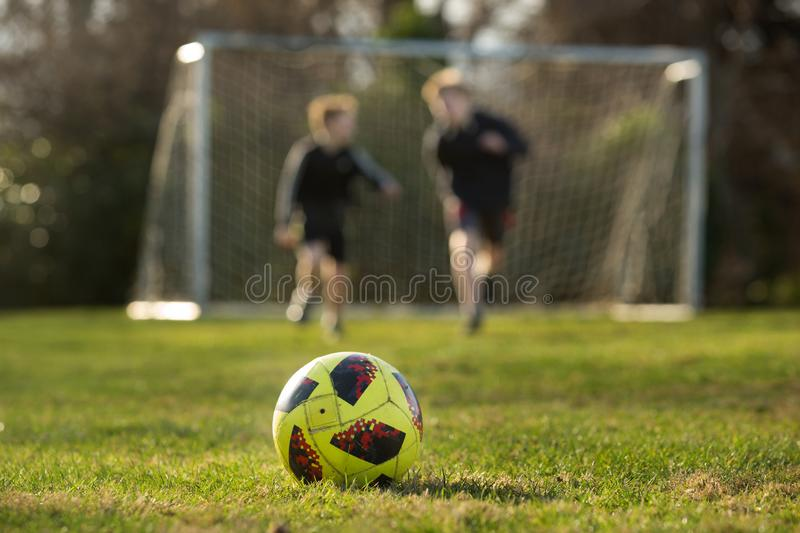 Two brothers race for a ball at the park stock photos