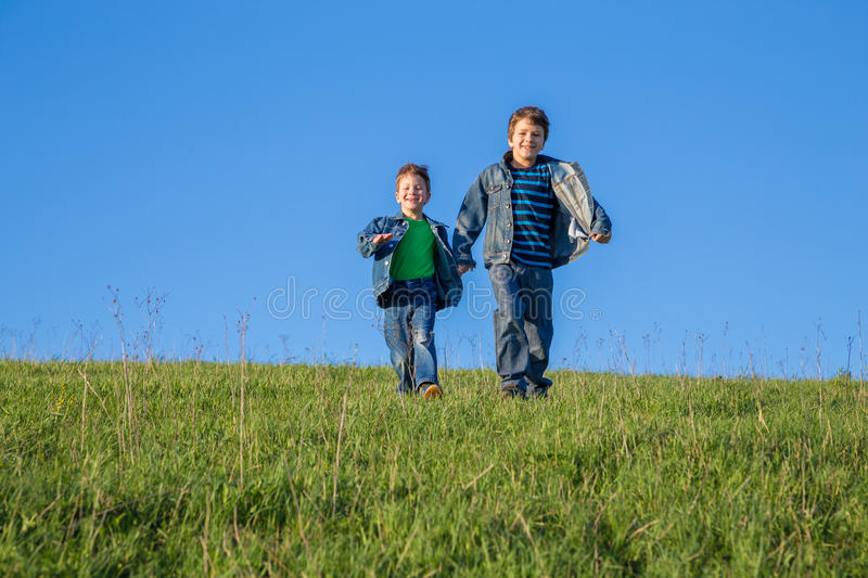 Two brothers running together on green meadow against blue sky stock image