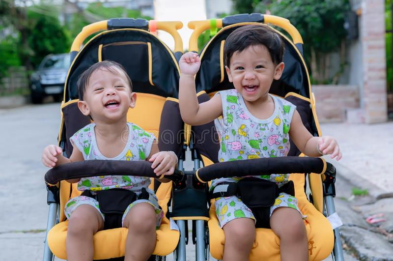 Two brothers sit in a stroller. Adorable twin baby boys sitting in stroller and smiling happily. Childhood emotions. Nursing twins royalty free stock images