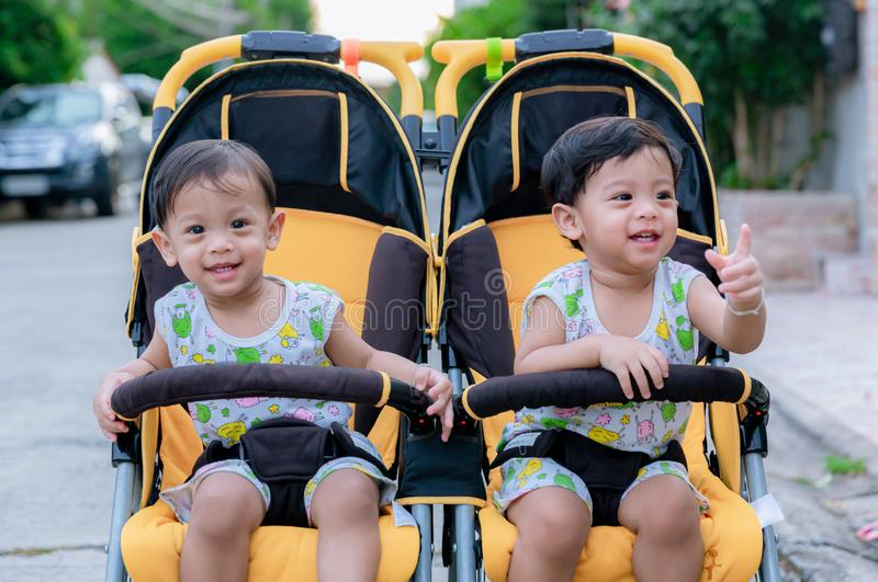 Two brothers sit in a stroller. Adorable twin baby boys sitting in stroller and smiling happily. Childhood emotions. Nursing twins stock photography