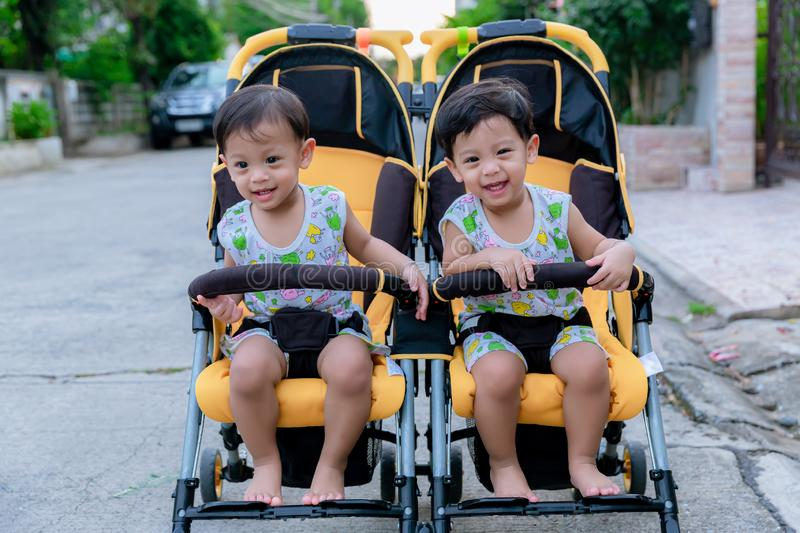 Two brothers sit in a stroller. Adorable twin baby boys sitting in stroller and smiling happily. Childhood emotions. Nursing twins royalty free stock photo