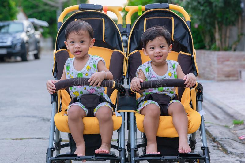 Two brothers sit in a stroller. Adorable twin baby boys sitting in stroller and smiling happily. Childhood emotions. Nursing twins stock photos