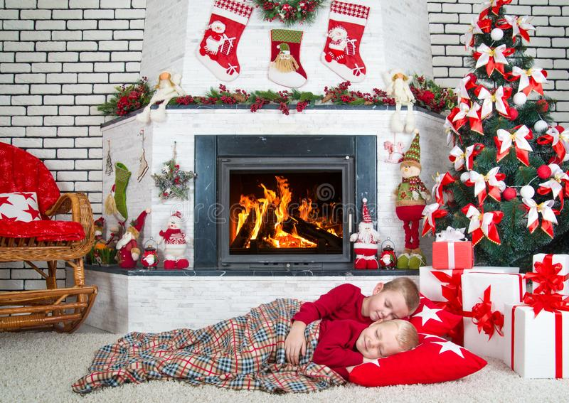 Merry Christmas and Happy Holidays!Two brothers sleep in the living room on the floor under the tree.In anticipation of gifts from. Two brothers sleep in the stock photo