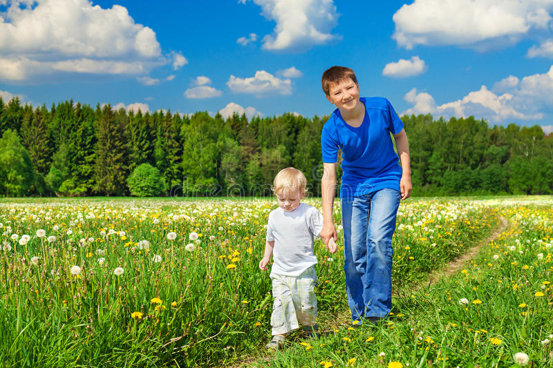 Two brothers, small child and teenager stock image