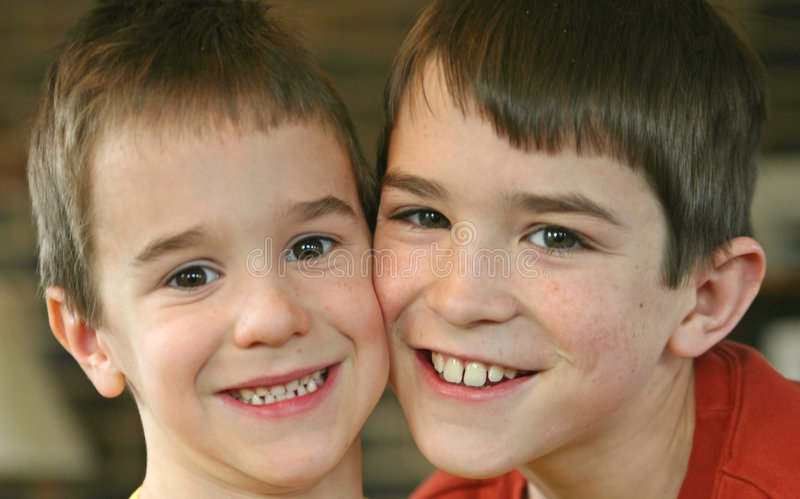 Two Brothers Smiling. With their cheeks together stock photo