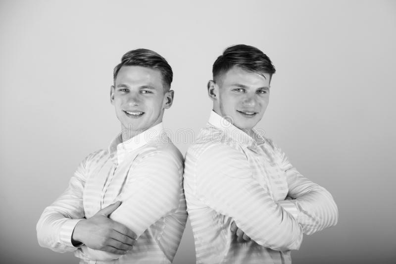 Two brothers smiling on pink background. Happy men with hands folded. Models standing together. Twins wearing blue shirts. Family, brotherhood and friendship royalty free stock photo