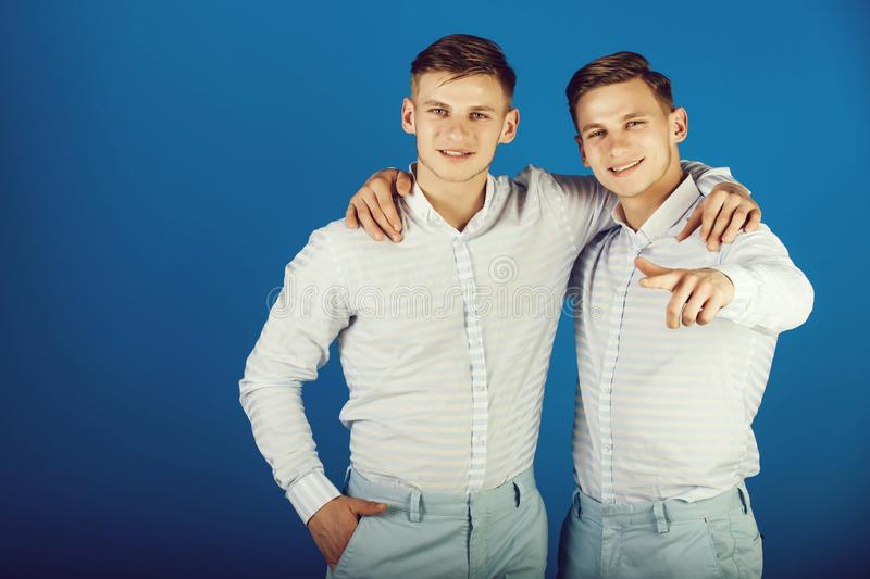 Two brothers smiling and pointing finger. Models standing on blue background. Twins wearing striped shirts and pants. Family, brotherhood and friendship stock images
