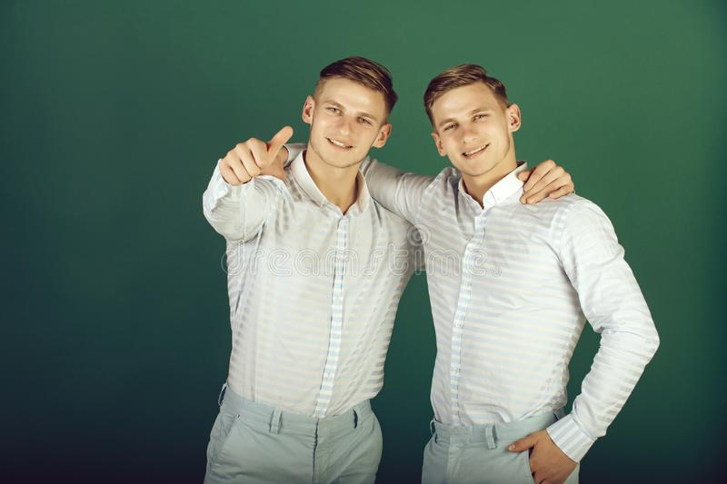 Two brothers smiling and pointing finger. Twins wearing blue shirts and pants. Happy men hugging. Models standing on green background. Family, brotherhood and royalty free stock photography