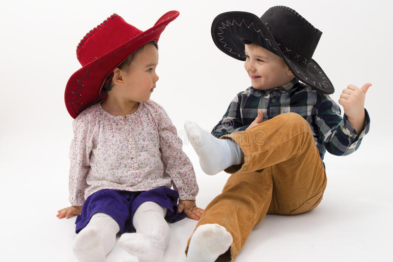 Two brothers smiling wearing cowboy hats isolated royalty free stock image