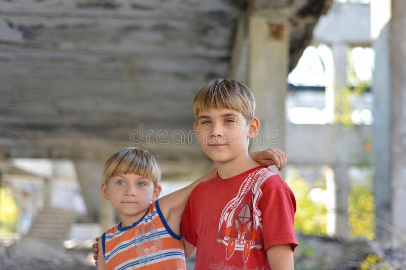 Two brothers are standing in an embrace against the backdrop of an unfinished and abandoned building, a concept of the life of stock photography