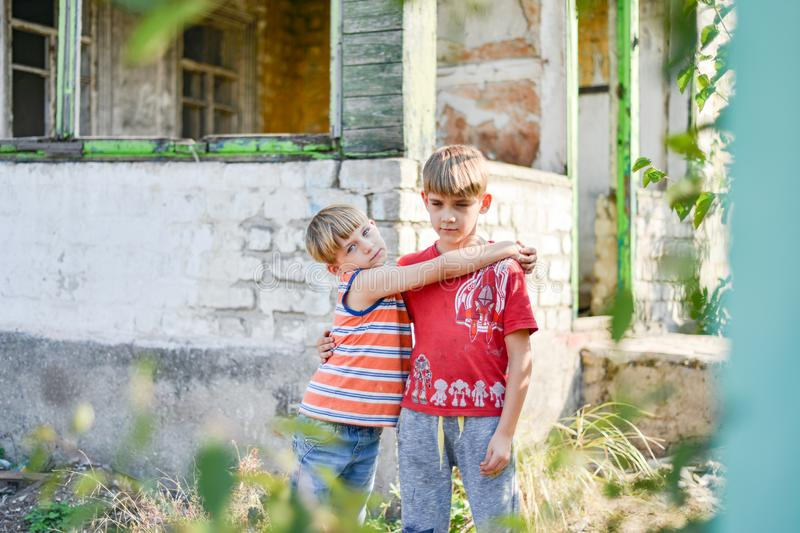 Two brothers are standing near a burned-out house, who lost their homes as a result of hostilities and natural disasters royalty free stock images