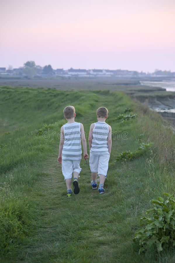 Two brothers walk away from camera royalty free stock photos