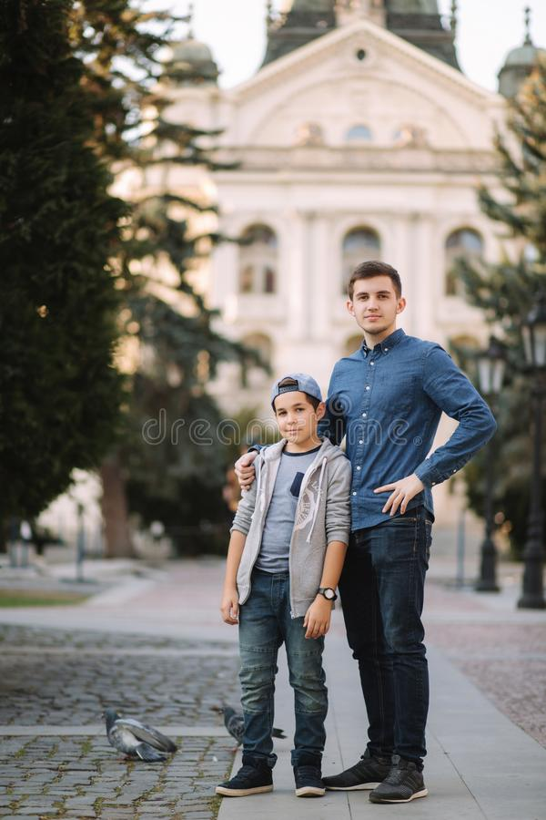 Two brothers walk in the city together. Happy family outside royalty free stock images