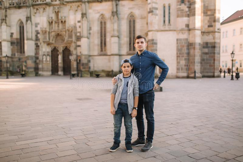 Two brothers walk in the city together. Happy family outside stock photography
