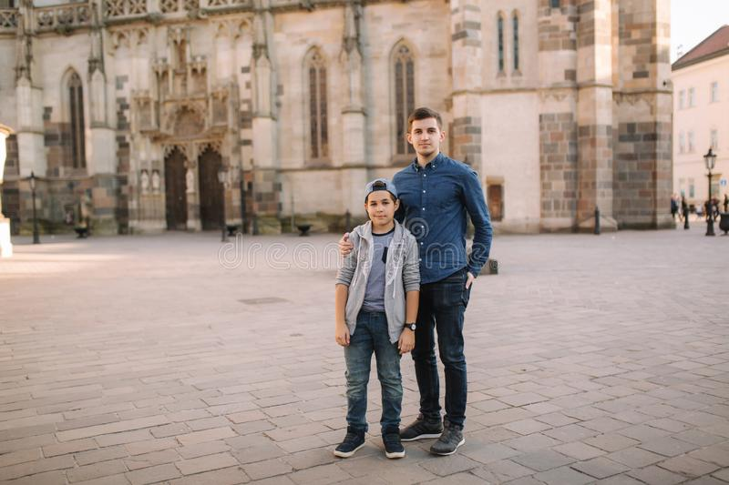 Two brothers walk in the city together. Happy family outside royalty free stock image