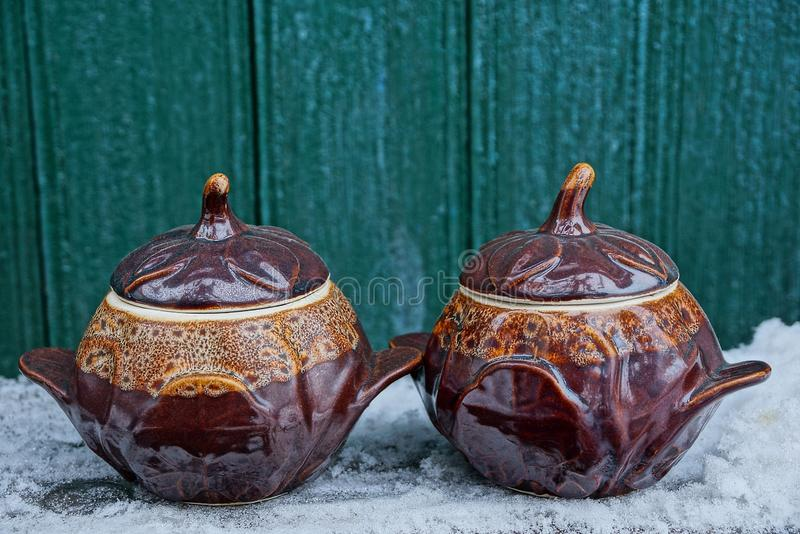 Two brown ceramic pots covered with lids on a table in white snow against a green wooden wall. Two brown ceramic pots covered with lids on a table in white snow stock photography