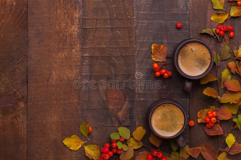 Two brown clay cups of black coffee and branches of autumn leaves Spiraea Vanhouttei with small red rowan`s fruits on the old wo. Oden table. Top view stock image