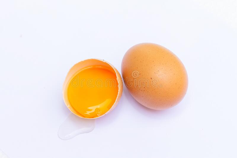 Two brown eggs With one egg broken in half, with a yolk inside the eggshell, laid on a white background royalty free stock images