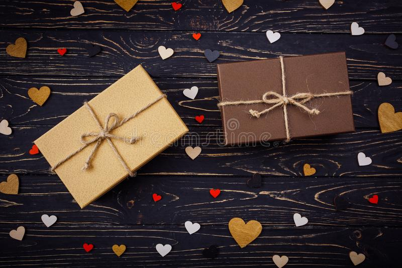 Two brown gift boxes on a wooden background with a bow of a simple rope on wood backgraund. Small decorative wooden hearts near box stock photo