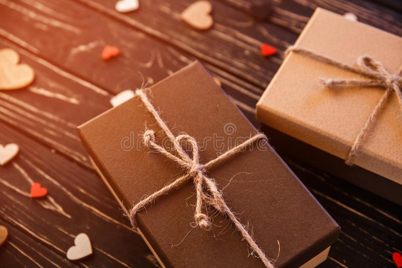Two brown gift boxes on a wooden background with a bow of a simple rope on wood backgraund. Small decorative wooden hearts near box stock images
