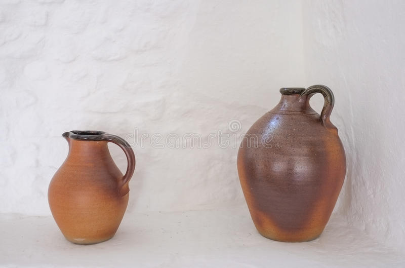 Two brown Pottery Jugs. Two brown traditional pottery clay jugs against a stone white wall background stock images