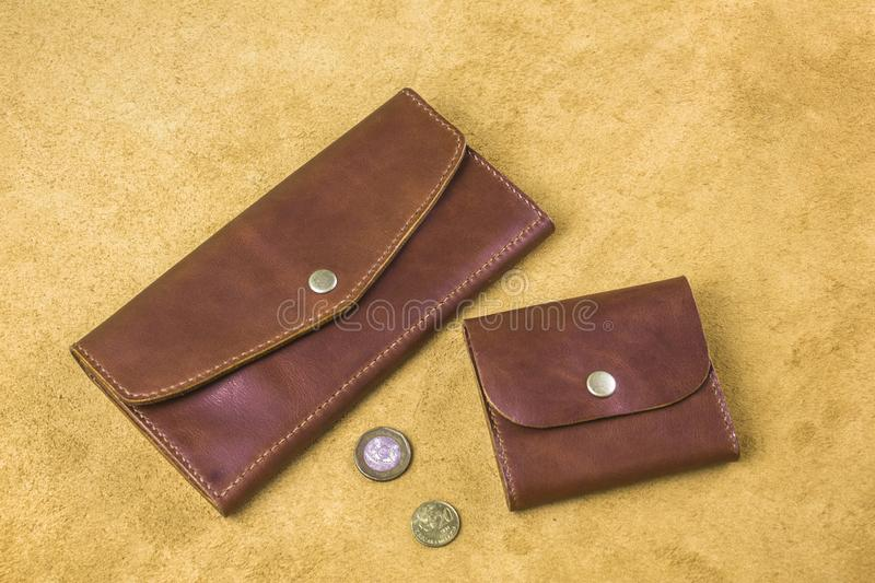 Two brown stitched purses of different sizes and shapes with coins on a yellow background stock photo