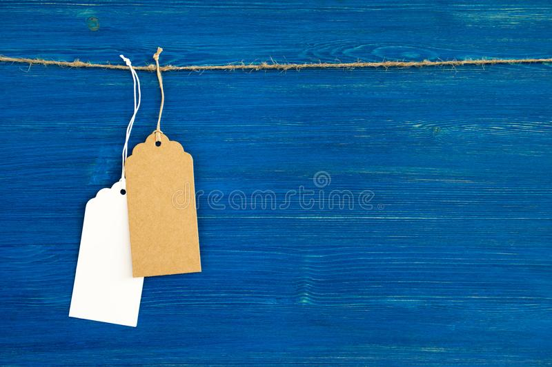 Two brown and white blank paper price tags or labels set hanging on a rope on the blue background. royalty free stock photography
