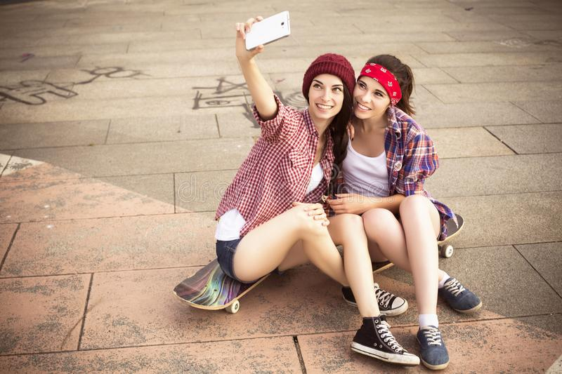 Two Brunette teenage girls friends in hipster outfit jeans shor royalty free stock photo
