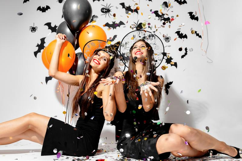 Two brunette women in witches hats smile, have fun with confetti and hold black and orange balloons. Halloween.  royalty free stock photography