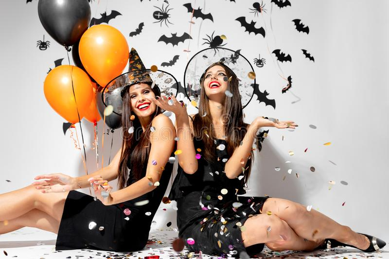 Two brunette women in witches hats smile, have fun with confetti and hold black and orange balloons. Halloween.  royalty free stock photos